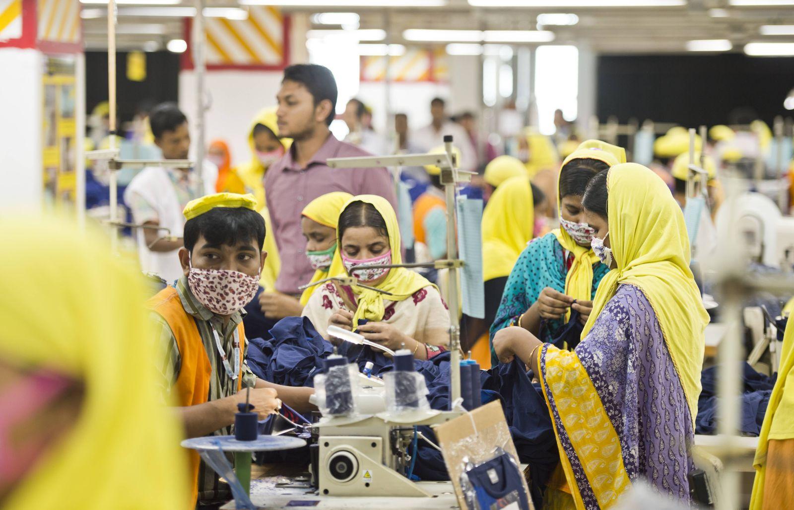 Naeherinnen und Schneider in der Textilfabrik der GBL Group, dem ersten Partnerunternehmen des Textilbuendisses in Bang