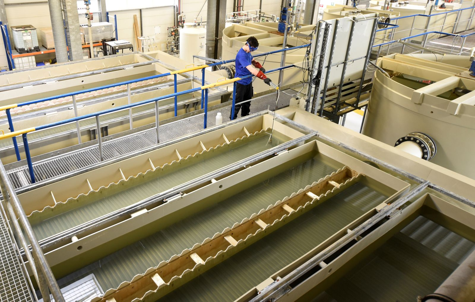 """A worker checks water in a water treatment factory, used to clear waste water from the paint shops, at the Volkswagen headquarters during a media tour to present Volkswagen's so called """"Blaue Fabrik"""" (Blue Factory) environmental program, in Wolfsburg"""
