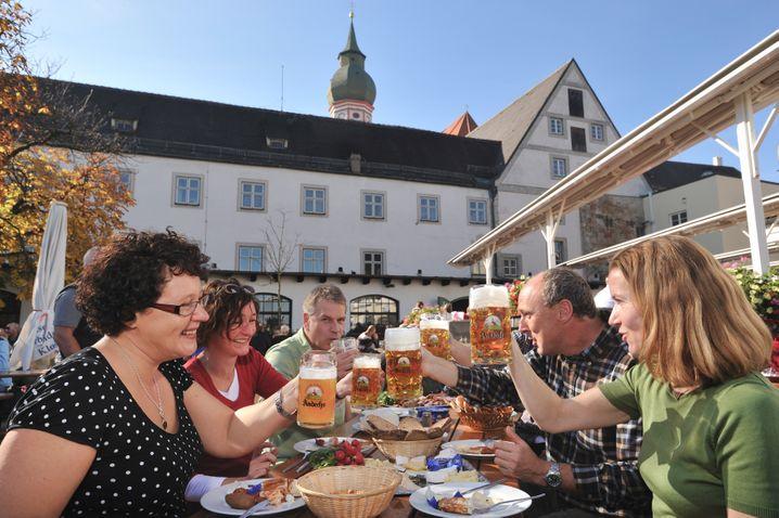 Junge Paare genießen die bayerische Gemütlichkeit an einem Biertisch auf der alten Bierterasse von Kloster Andechs