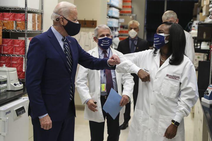 Ellenbogencheck mit dem Präsidenten: Die Forscherin Kizzmekia Corbett und US-Präsident Joe Biden begrüßen sich im Vaccine Research Center (VRC) des National Institute of Allergy and Infectious Diseases während eines Rundgangs mit Institutsdirektor Anthony Fauci (Mitte)