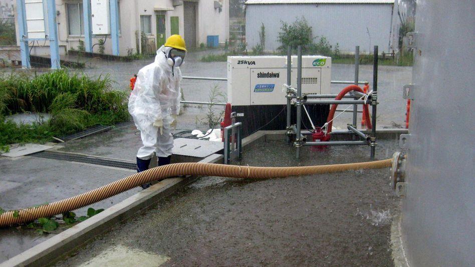 Immer wieder Zwischenfälle: Ein Arbeiter der Betreiberfirma Tepco pumpt Regenwasser ab, das die Tanks mit radioaktiv verstrahltem Kühlwasser umspült hat