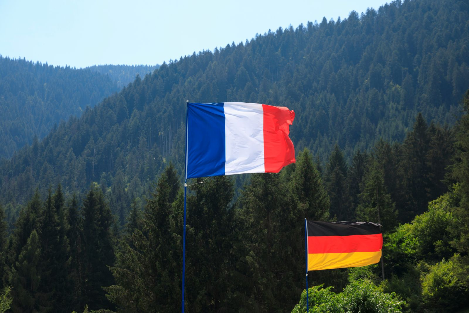 French flag and German flag fluttering in the wind.