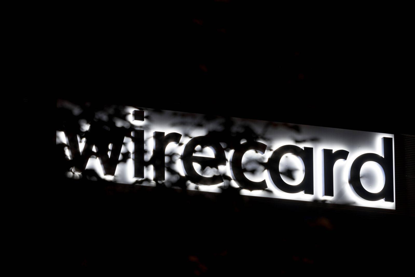 Wirecard Firmenlogo bei Nacht Im Bild Firmenlogo beleuchtet teilweise verdeckt Baum Bl?tter Verdunklung Verschleierung.