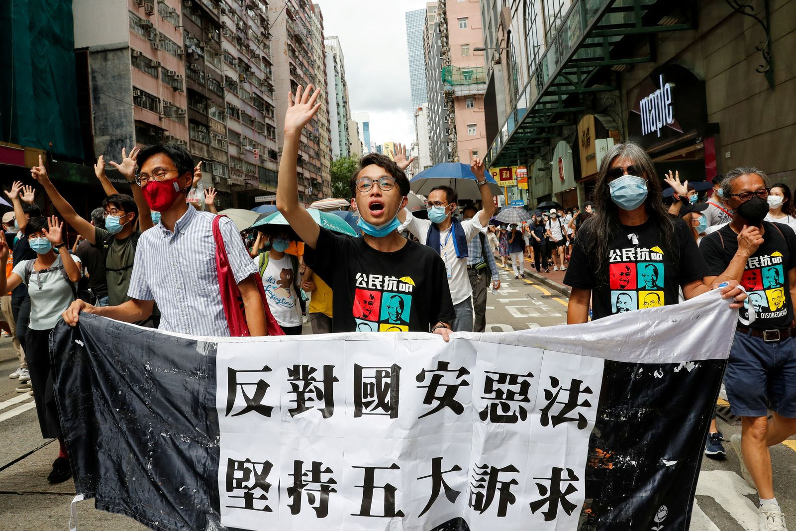 Pan-democratic legislator Eddie Chu Hoi-dick, Vice convener for Hong Kong's Civil Human Rights Front Figo Chan and activist Leung Kwok-hung march at the anniversary of Hong Kong's handover to China from Britain, in Hong Kong