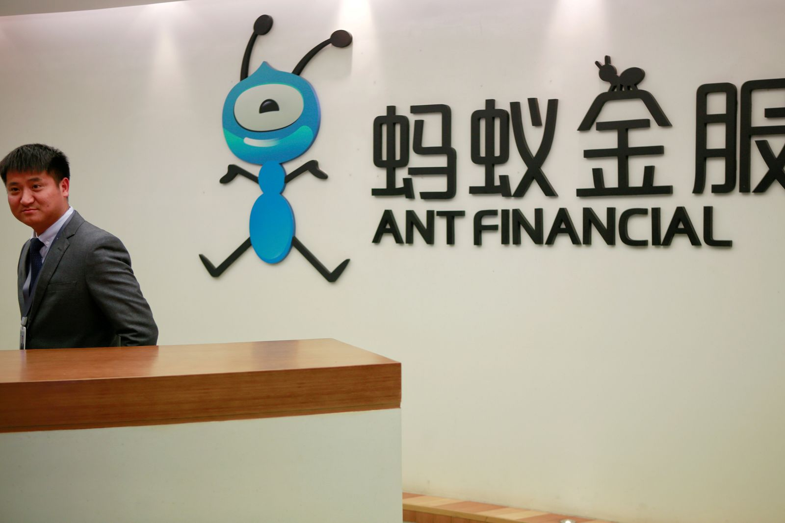 FILE PHOTO: Employee stands next to the logo of Ant Financial Services Group at its headquarters in Hangzhou, China