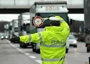 Herauswinken litauischer Lastwagen: Ein Beamter des Bundesamtes für Güterverkehr will potenzielle Mautpreller kontrollieren