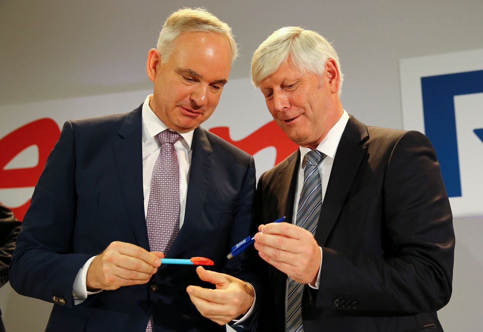 RWE and E.On CEOs Schmitz and Teyssen exchange pens following a news conference in Essen after unveiling plans for an asset swap between the two German utilities