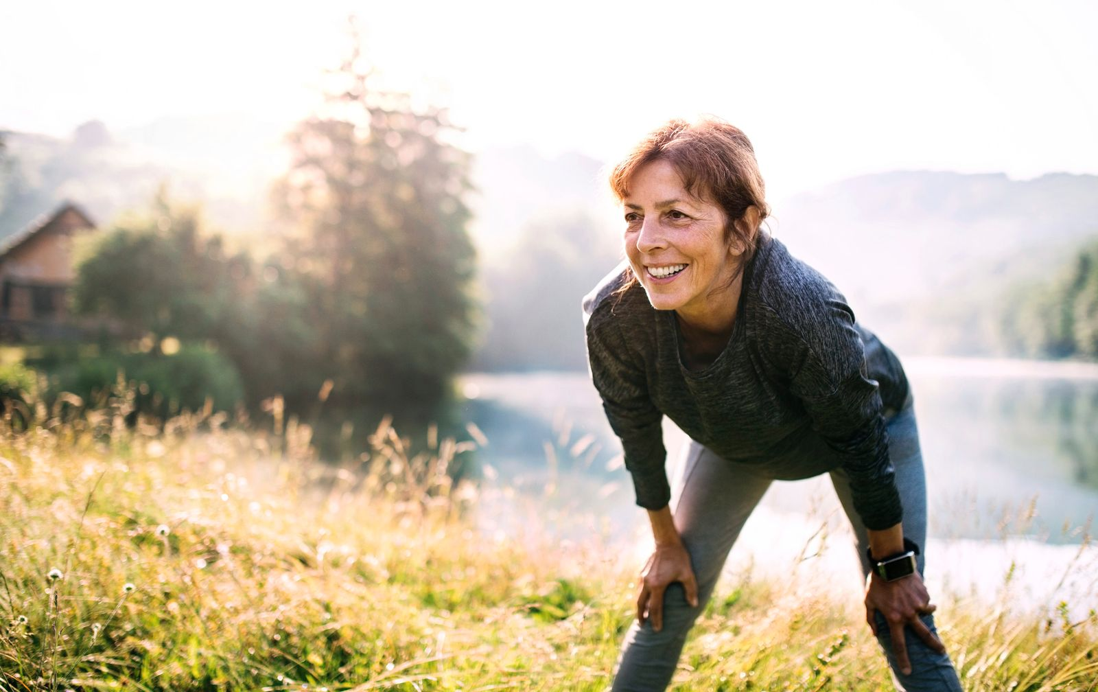 Senior woman resting after exercise outdoors in nature in the foggy morning. Copy space.