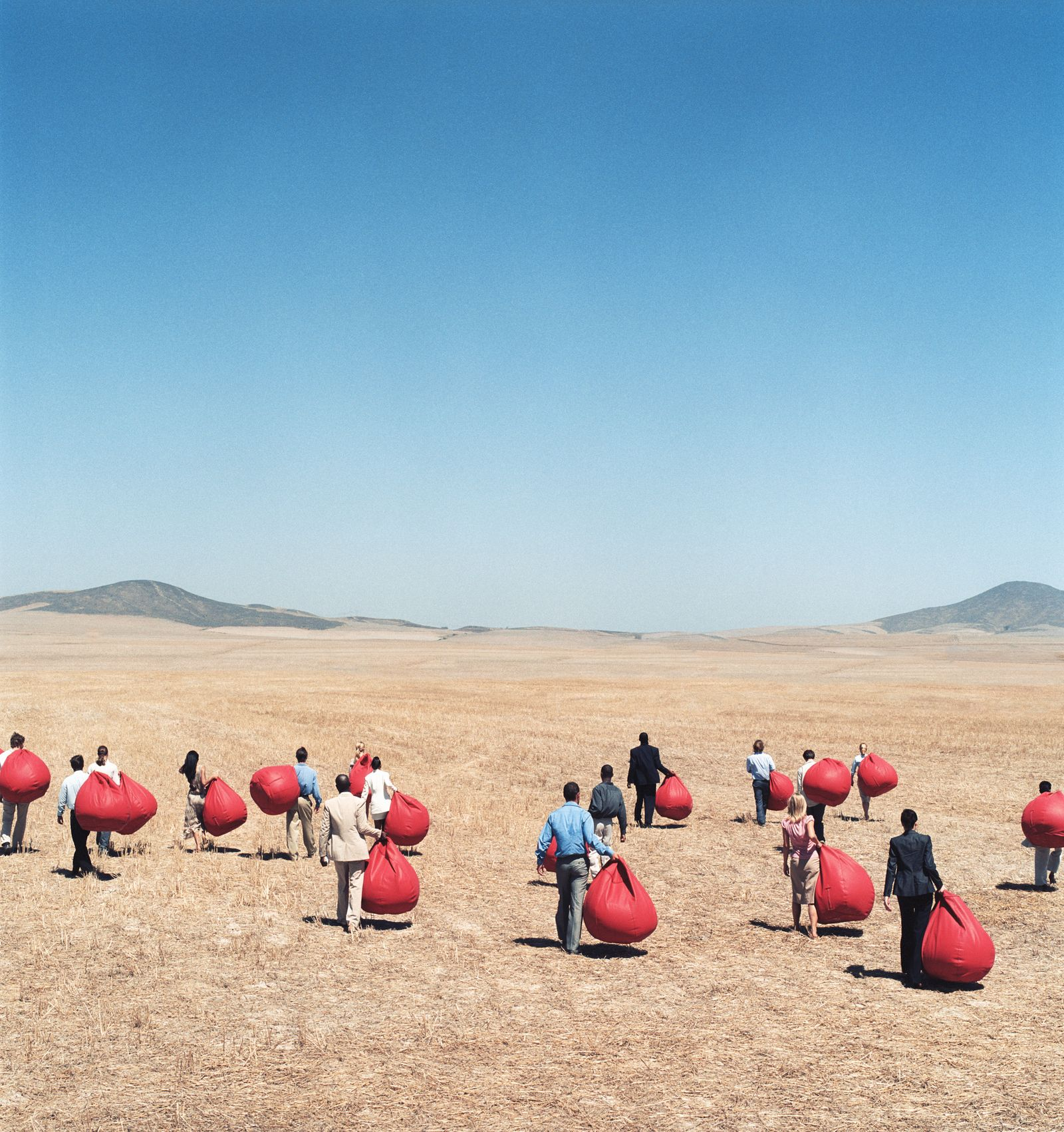 Group of business people carrying bean bags in open landscape