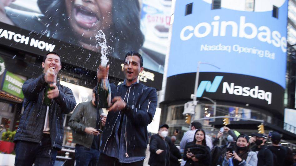 Champagnerlaune: Mitarbeiter und Fans von Coinbase feiern das Börsendebüt auf dem New Yorker Times Square vor der Nasdaq-Anzeige