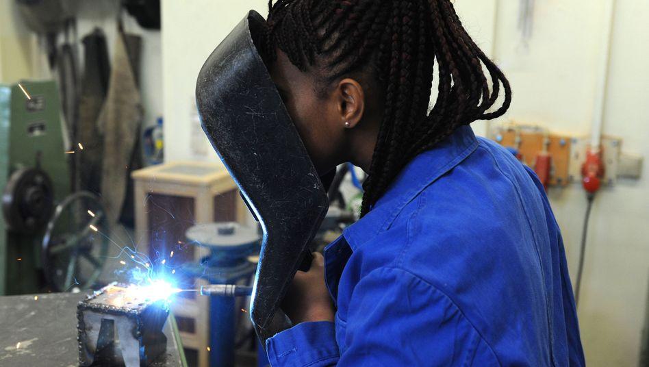 Flüchtlingen in der Ausbildung: Die Schülerin Hadeiatou aus dem afrikanischen Guinea absolviert in der Metallwerkstatt der Allgemeinen Berufsschule in Bremen einen Kurs im E-Schweißen. Die junge Frau gehört zu den Flüchtlingen, denen es gelang, ihr Leben nach Deutschland zu retten und hier eine Ausbildung zu beginnen