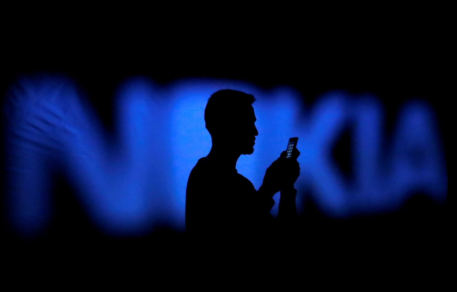 FILE PHOTO: A photo illustration of a man silhouetted against a Nokia logo