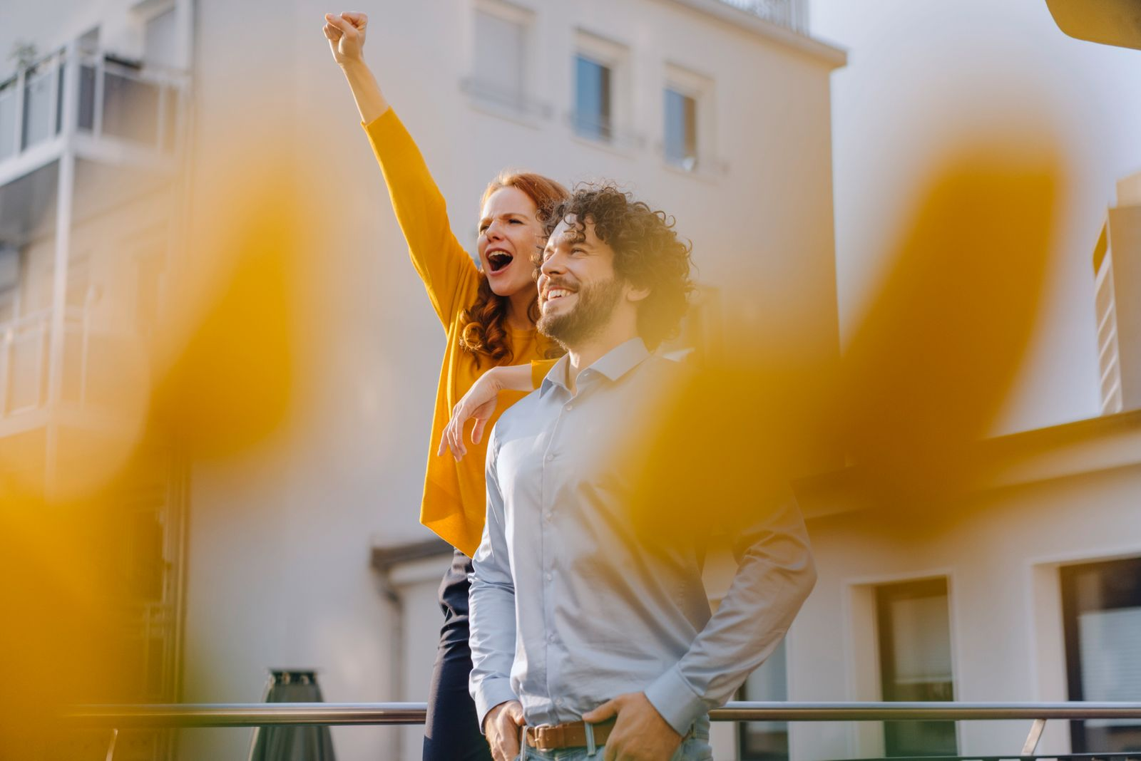 Woman with colleague on roof terrace clenching fist