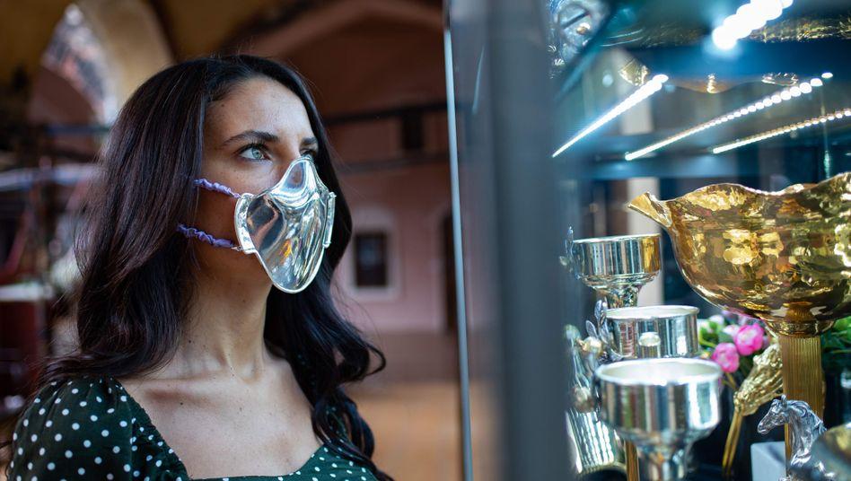 Edelmetall als Krisenschutz: Kundin mit Silbermaske vor Laden eines Gold- und Silberschmieds in Istanbul
