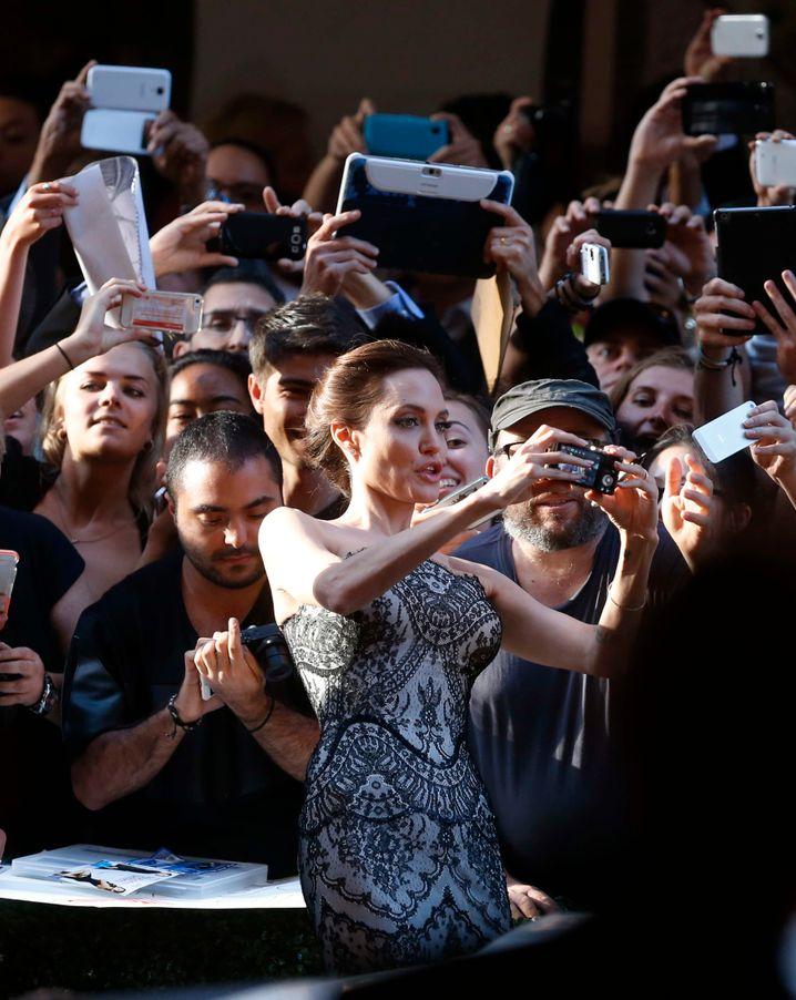 Keine Spur unsicher: Angelina Jolie beim Posieren mit Fans. Aber auch für Normalos kann die Kamera ein ehrlicher Freund sein.