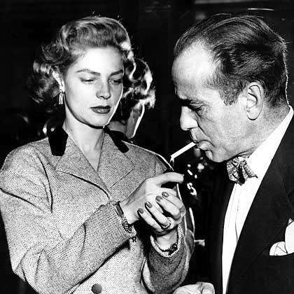 Wohl bekomms: Lauren Bacall lights entflammt ihres Ehemannes Zigarette. Humphrey Bogart starb an Kehlkopfkrebs.