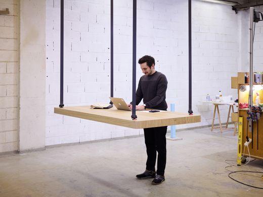 Stehpult:Der Eichentisch lässt sich auf individuelle Arbeitshöhen einstellen, wie ErfinderJean-Christophe Petillaultzeigt. Tischab 7000 Euro.