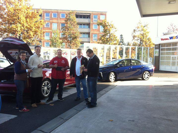 Treffen an der Tankstelle in Berlin: Unser Wasserstoff-Auto Toyota Mirai (blau) wird es ab 13 Uhr mit zwei Tesla-Elektroflitzern (im Bild die beiden Tesla-Crews) aufnehmen. Wer ist zuerst im nordbayerischen Geiselwind?