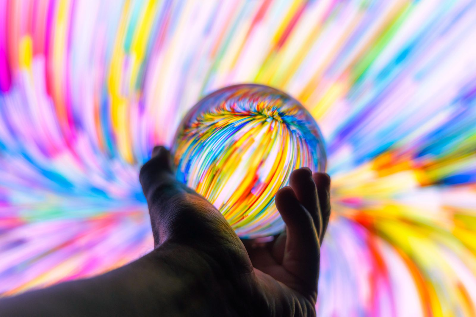 Holding a crystal ball through colorful background at night.