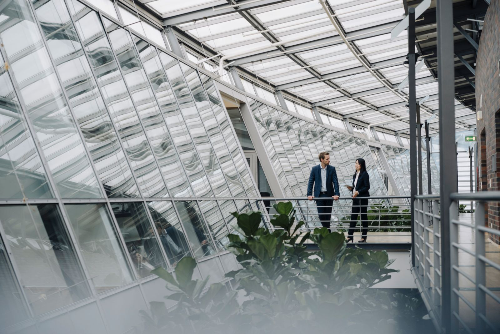 Businessman and businesswoman standing on a skywalk in modern office building