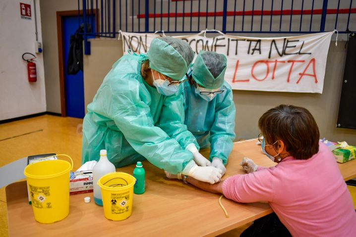 Medizinische Mitarbeiter in Schutzanzügen entnehmen eine Probe für serologische Tests zur Erfassung von Antikörpern für Covid-19. Die Zahl der neuen Infektionsfälle ist am Mittwoch in Italien wieder schneller gestiegen.