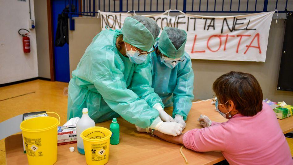 Italien: Medizinische Mitarbeiter entnehmen eine Probe