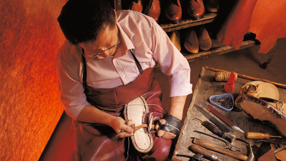 Schuhmacher bei der Arbeit: Mehr Handarbeit kostet mehr, hält aber auch länger - und ist Ausweis ausgeprägten Stilempfindens