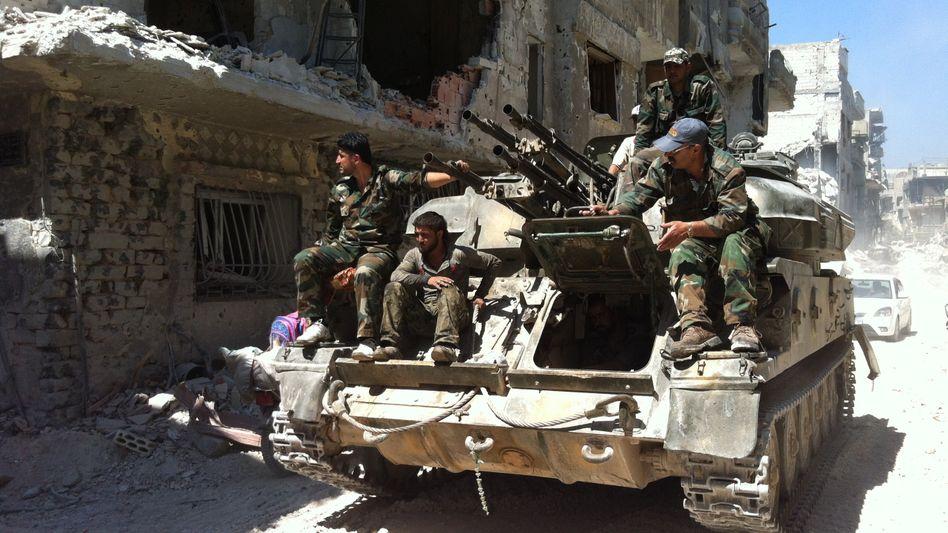 Syrische Soldaten in der Stadt Homs: Trotz Angriffsdrohungen gehen die Kämpfe weiter.