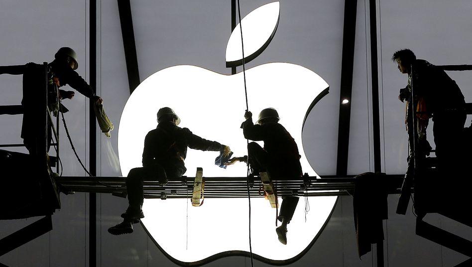 Arbeiter in China vor einer Apple-Filiale