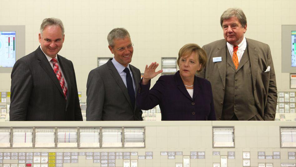Streit um die Energie der Zukunft: Eon-Chef Johannes Teyssen (links) und RWE-Chef Jürgen Großmann (recht, im Bild mit Kanzlerin Merkel und Umweltminister Norbert Röttgen im AKW Lingen) müssen einen Vertrauensverlust unter den Wirtschaftslenkern hinnehmen