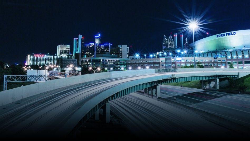 AUFBRUCH IN MOTOR CITY GM (Zentrale im Hintergrund) und Ford pumpen Milliarden in Robotertaxis, auch Google kommt nach Detroit