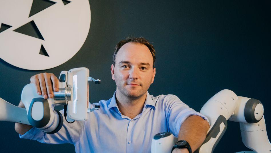 Der Kopf hinter dem Arm: Simon Haddadin, CEO von Franka Emika, umgeben von seinen Panda-Robotern. Bis 2015 will er eine Million davon verkaufen.
