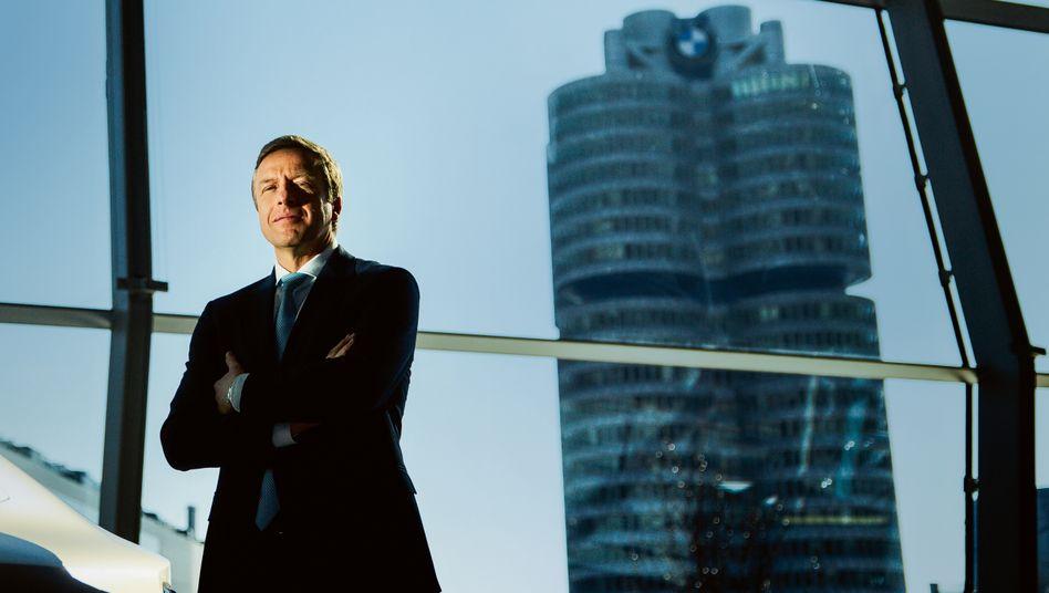 Herr über den Vierzylinder: Oliver Zipse neben einem i4 in der Ausstellung BMW-Welt, im Hintergrund die Konzernzentrale.