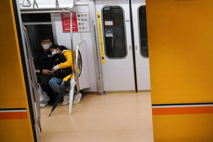Paar mit Gesichtsschutzmasken in einer U-Bahn in Tokio: Weil viel zu wenig Menschen auf das Coronavirus getestet werden, warnen Ärzte in Japan nun vor einem Zusammenbruch des Gesundheitssystems.