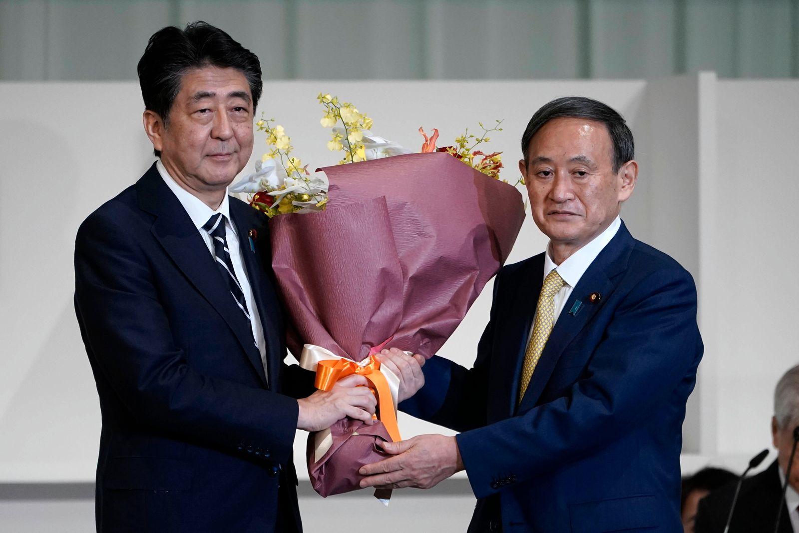 September 14, 2020, Tokyo, JPN: Japan s Prime Minister Shinzo Abe, left, presents Chief Cabinet Secretary Yoshihide Sug