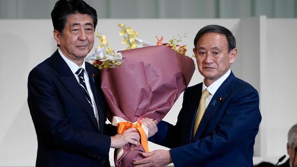 Shinzo Abe (l.) überreicht YoshihideSuga nach seiner Wahl Blumen