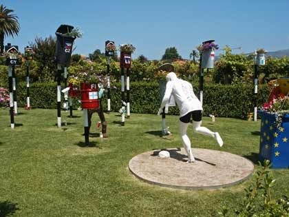 Installation: In einem der Gärten in Ponte de Lima sind lauter Papierkörbe aufgestellt, aus denen Blumen wachsen und auf die ein Fußballspieler zielt