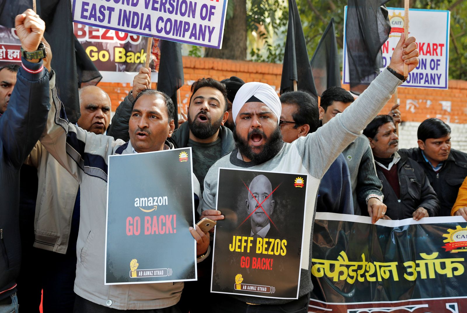 Members of the Confederation of All India Traders hold placards and shout slogans during a protest against the visit of Jeff Bezos to India, in New Delhi