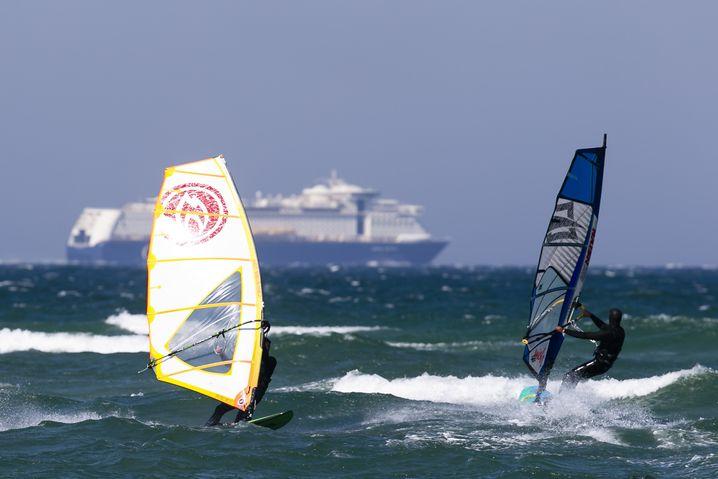 Heidkate: Zwei Windsurfer gleiten bei strahlendem Sonnenschein und Ostwind auf der Ostsee, während ein Fährschiff im Hintergrund zu sehen ist.