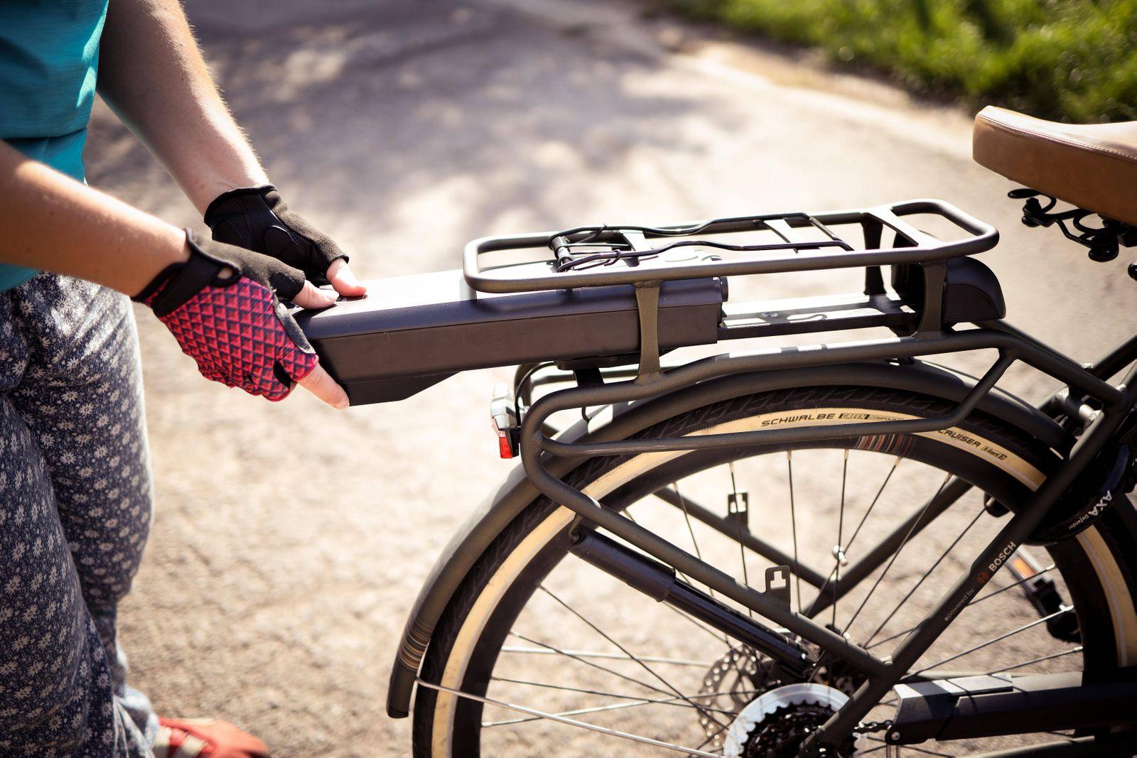 Radfahrerin beim Einsetzen der Batterie an einem Elektrofahrrad, Belgien, Europa *** Cyclist inserting the battery on an