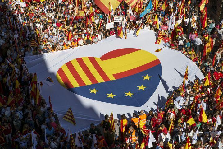 Demonstranten halten ein Banner mit einem Herz aus den Flaggen Kataloniens, Spaniens und Europas