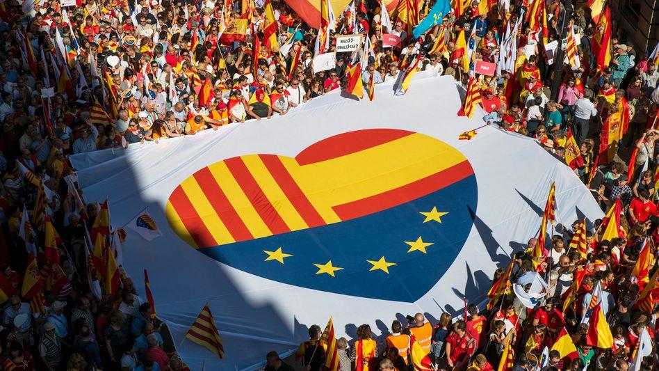 Protest der anderen Art: Demonstranten tragen ein Banner mit einem aus den Flaggen von Katalonien, Spanien und Europa durch die Straßen von Barcelona. Sie protestieren damit gegen die Abspaltungspläne der Regionalregierung in Barcelona