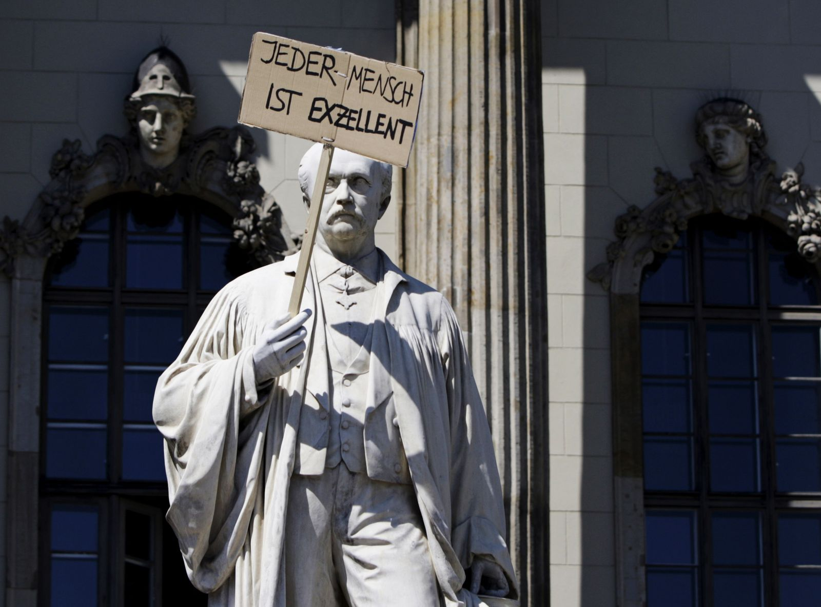 People hold banners in front of the Humbold University during a protest during protest by pupils and students in Berlin