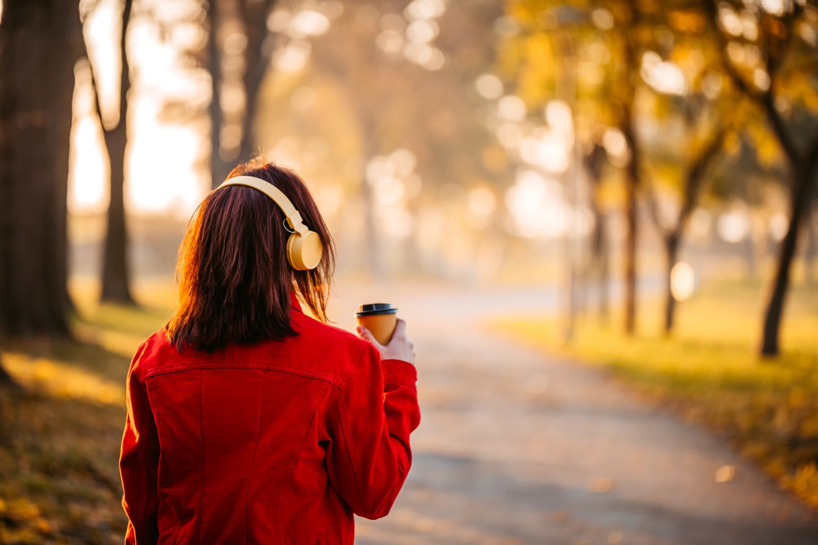 Woman drinking coffee listening music in park