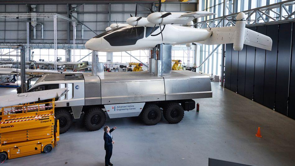 Konzernriesen, Forschende und Start-ups setzen auf Klimainnovation: So auch die Projektteams um Tim Mackley (im Bild mit einem elektrischen Flugzeug), die an der britischen Cranfield-University saubere Flugkonzepte der Zukunft entwickeln