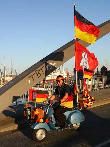 Fan: Zur Begrüßung des Schiffes hat sich der Vespa-Fahrer eine rollende Deutschlandfahne gebaut