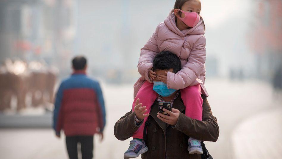 Wie hier in Peking versuchen sich die Menschen in China mit Schutzmasken vor einer Ansteckung zu schützen