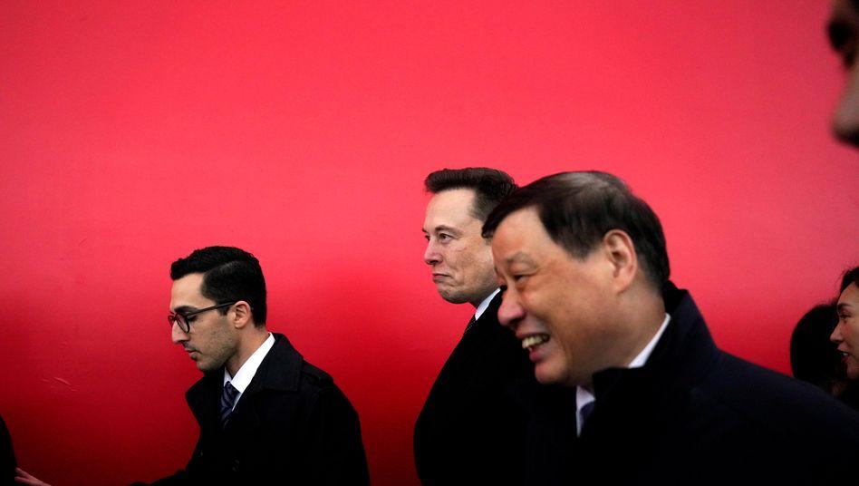 Tesla-Chef Musk (Mitte) in Shanghai: Der Autobauer steht unter Druck, weil die Produktion und der Verkauf des Model 3 nicht zufriedenstellend laufen.