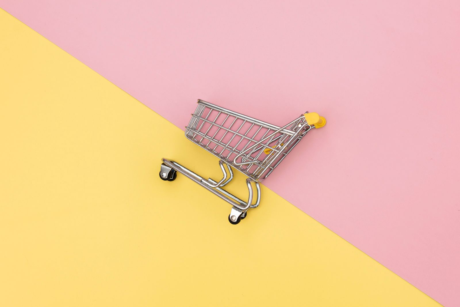 Metal shopping cart on pink and yellow backgrounds.