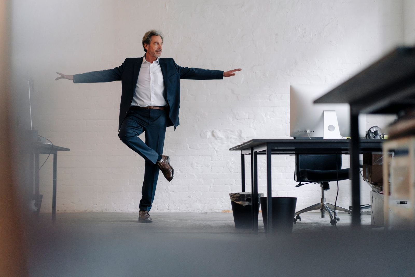 Senior businessman doing a yoga exercise in office